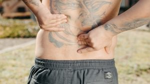 A Faceless Man Rubbing His Lower Back
